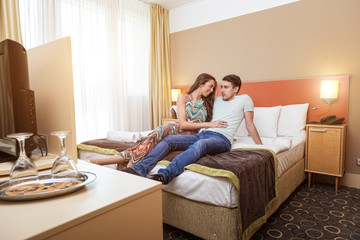 Young couple's arrival to the hotel, sitting on the bed
