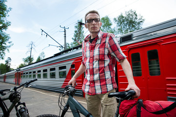 Tourist with bikes and luggage on suburban railway platform wait
