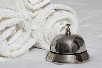Room service bell and rolled towels.
