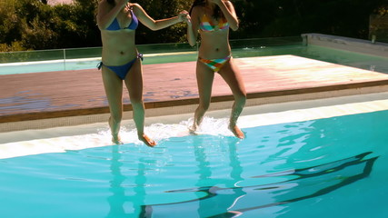 Happy friends jumping into swimming pool together