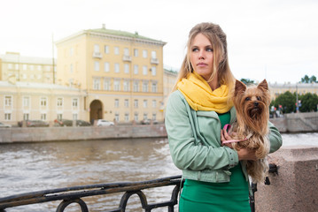 Sad young woman with little dog in city