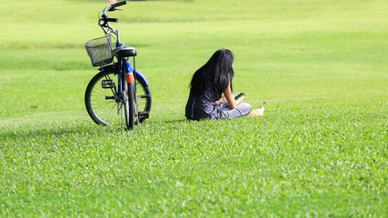 Girl using her mobile phone outdoors near bicycle