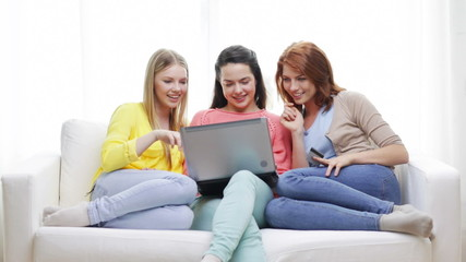 smiling teenage girls with laptop and credit card
