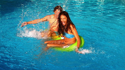 Young couple splashing and having fun in swimming pool