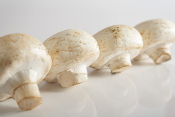 Fresh, white mushrooms in line.  Selective focus.