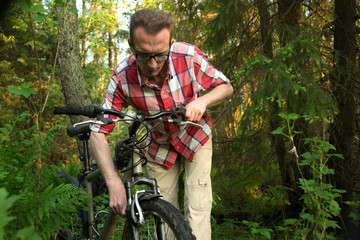 Tourist, repearing his bike in the woods
