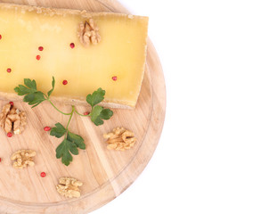 Cheese on wooden platter with walnuts.