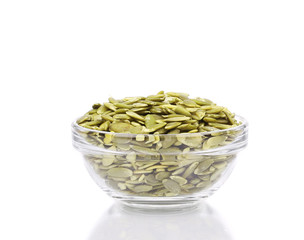 Glass bowl full with pumpkin seeds.