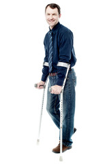 Man walking with crutches isolated on white