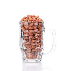 Glass mug full with peanuts.