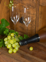 A bottle of white wine, glasses and bunch of grapes