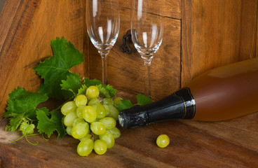 A bottle of wine with a bunch of grapes and wineglasses