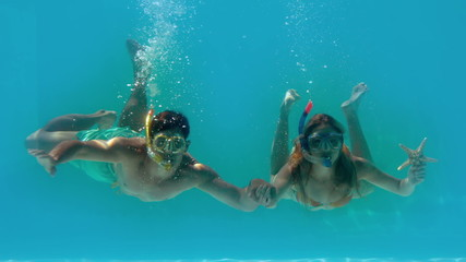 Couple wearing snorkels holding starfish underwater