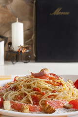 Spaghetti with smoked salmon on table.