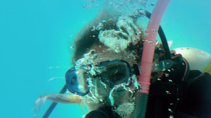 Woman in scuba gear looking at camera underwater