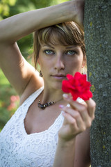 Attractive woman holding out a red rose