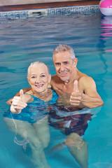 Paar Senioren hält Daumen hoch im Wasser