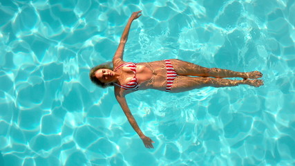 Woman floating in the swimming pool