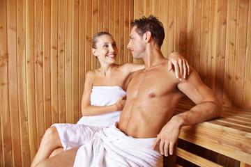 Glückliches Paar sitzt in der Sauna