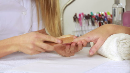 Nail technician filing customers nails