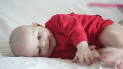 Baby in a red t-shirt tries to catch the foot