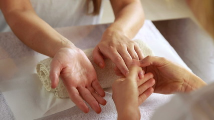 Beauty therapist massaging customers hands