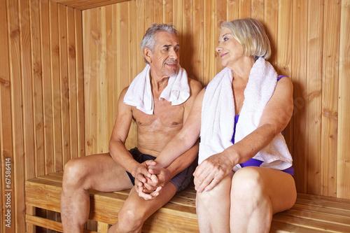 Zwei Senioren halten Hände in Sauna