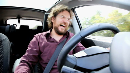 Man laughing while driving car talking on phone