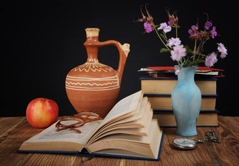 Apple, books and flowers in a vase