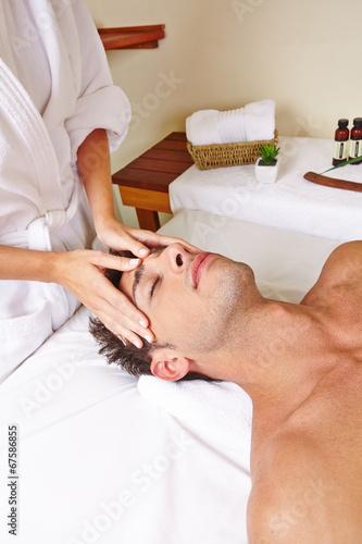 Hände einer Maseurin berühren Mann am Kopf