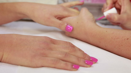 Nail technician applying pink varnish to customers nails