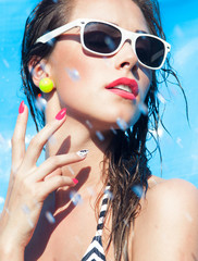 Young attractive woman wearing sunglasses by the swimming pool