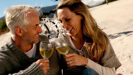 Happy couple drinking white wine on the beach