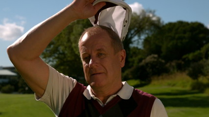 Mature golfer taking off his cap on a hot day