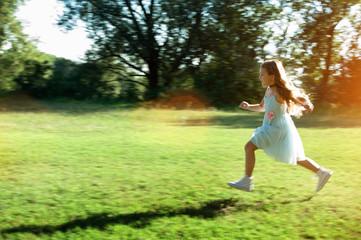 Bambina che corre nell'erba