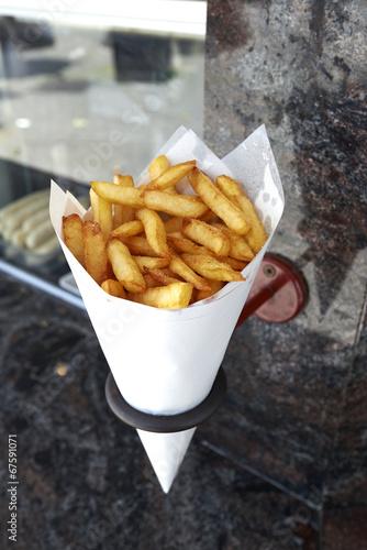 Deurstickers Klaar gerecht Potatoes fries in a little white paper bag hanging at the wall f