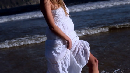 Beautiful blonde walking in white dress on sunny day at the beac