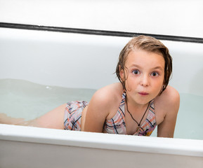 Little girl bathes in a bathroom.