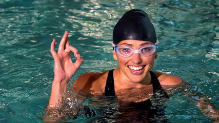 Fit female swimmer showing ok sign in the swimming pool