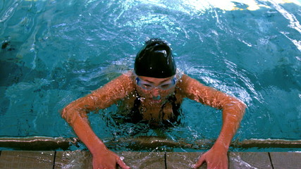 Fit swimmer emerging from pool and pulling herself up
