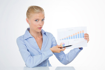 blond business woman looking at the camera holding a chart