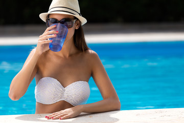 Beautiful girl drinking water at the swimming pool.