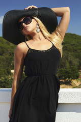 Beautiful blond woman in Black Hat and Sunglasses.the roof