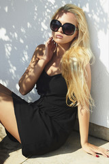 beautiful blond woman.girl in sunglasses near the wall