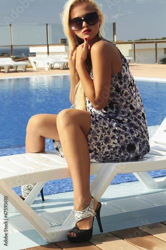 beautiful woman in sunglasses near pool.blond girl in high heels