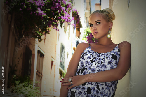 Beautiful blond woman in old town.girl in colored dress.flowers