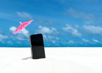 Mobile phone and cocktail umbrella on the beach