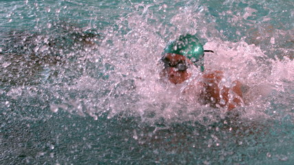 Muscular swimmer doing the butterfly stroke in the pool