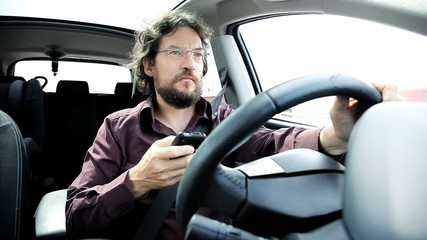 Man texting cell phone while driving car