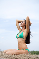 Young slim model in a green bikini
